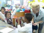 BtB volunteer encourages and supervises a pair of students learning to use digital cameras.
